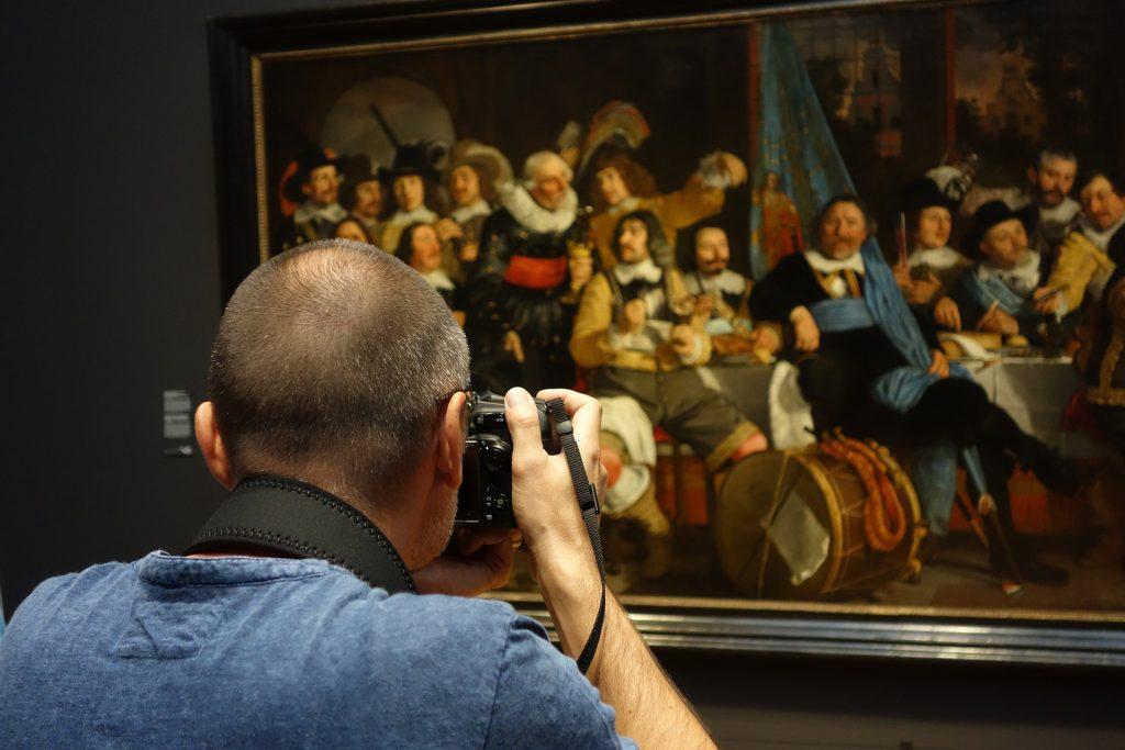 Mann fotografiert ein Gemälde in einem Museum urheberrechtlich erlaubt