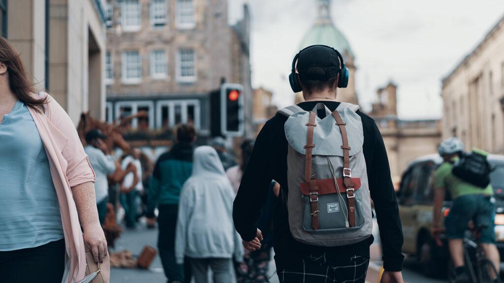 Symbolbild für Audiowalk - Person mit Kopfhörern unterwegs auf der Straße